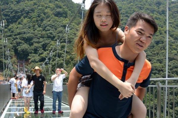"""广东景区现""""玻霸保镖"""" 每天平均背30名游客过玻璃桥"""