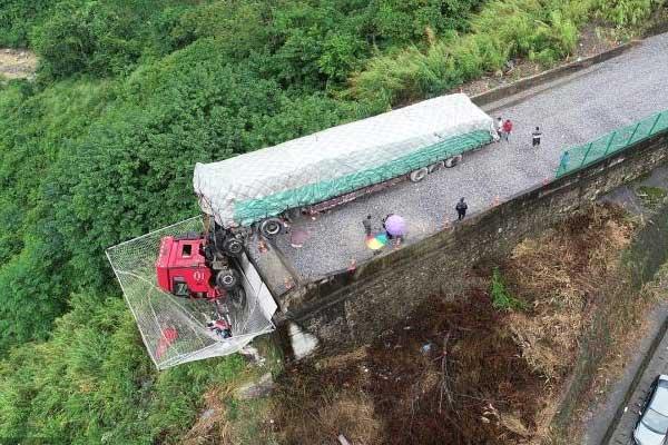货车失控挂在悬崖边 网兜兜住车头救人命