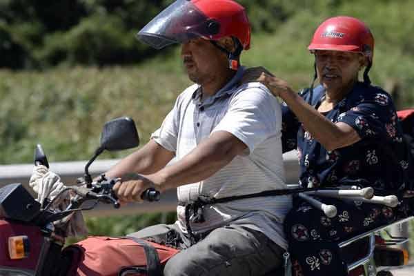 八旬老人高温天把自己绑在摩托上 去给孩子上课