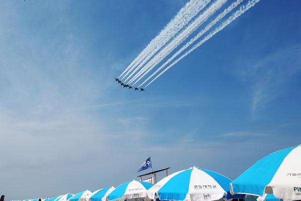 韩国空军黑鹰特技飞行队献技 海滩游客边避暑边赏飞行大片