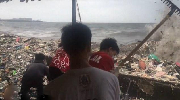 海浪裹挟垃圾袭击菲律宾海岸 环保人士冒险清理
