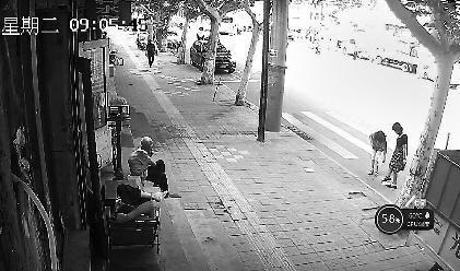 緊接著,一名穿淺色衣服的女子走過來用手機對著路邊的商戶拍照,然后又