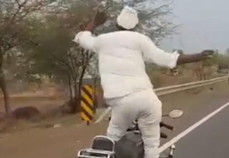 印老人摩托车上平躺翘二郎腿舞动身体惊呆众人