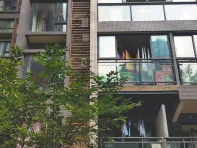 小区藏84家旅馆:住户窗户上张贴着住宿等广告