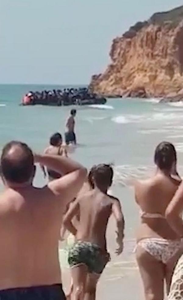 约50名非法移民登陆西班牙海滩爬悬崖 惊呆游客