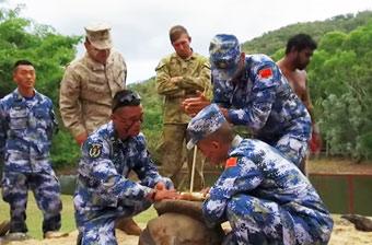 中美澳士兵共同演练野外求生 学习钻木取火