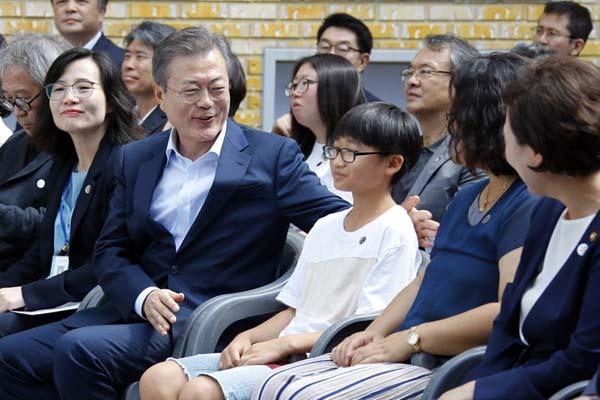 韩国总统文在寅参观村图书馆 与儿童并坐交谈