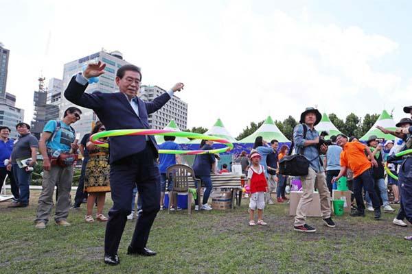 首尔市长参加社区活动 转呼啦圈踢足球秀亲民