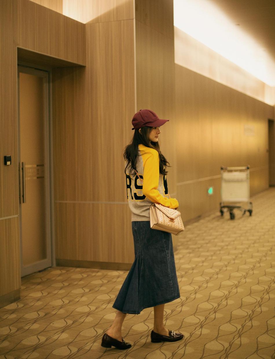 杨幂启程纽约时装周 字母上衣搭牛仔半裙潇洒时尚
