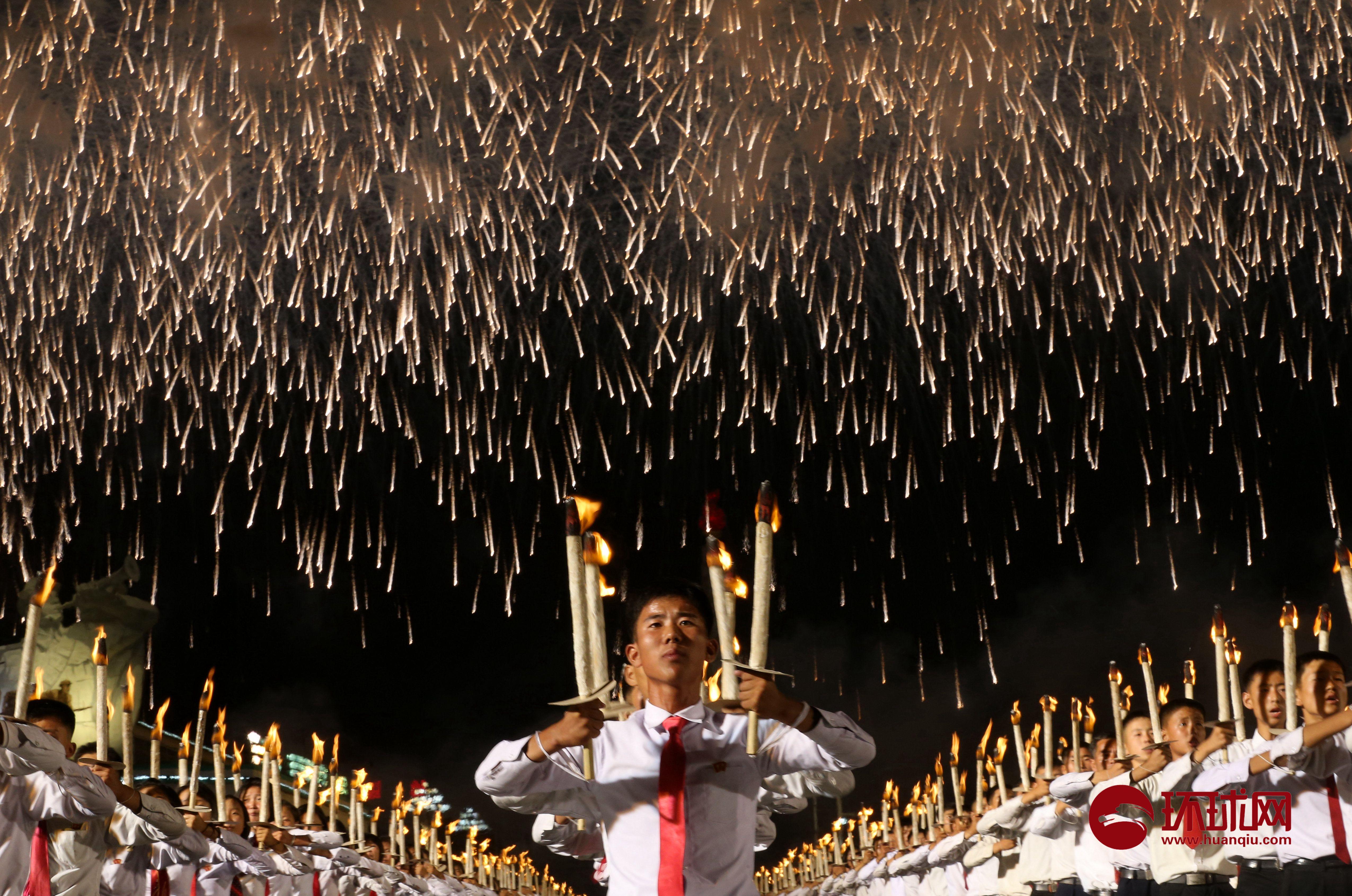 10日晚,为庆祝朝鲜建国70周年,平壤金日成广场举行主题为《前进吧!青年们》的火炬及烟花表演,几千名手持火炬的学生排列成各种文字和图案,再次向世界展示了集体的气势。本次活动持续约一小时,比往年时间短。最令记者们惊讶的是面对广场站立的火炬手,他们竟一直保持两手持火炬,且上臂与肩膀齐平的姿势,从演出开始到结束纹丝不动!