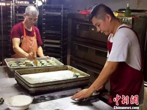 陈立新与陈超雄父子在制作传统豆沙月饼李晓春摄