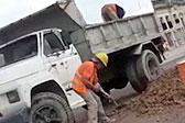 阿根廷街头一人给车装土 一人向下卸土
