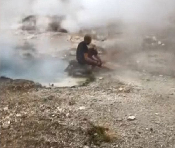 美黄石公园间歇泉游客热汽中淡定洗脚
