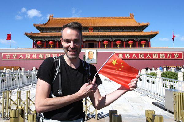 迎国庆,游客手举国旗在天安门前拍照留影