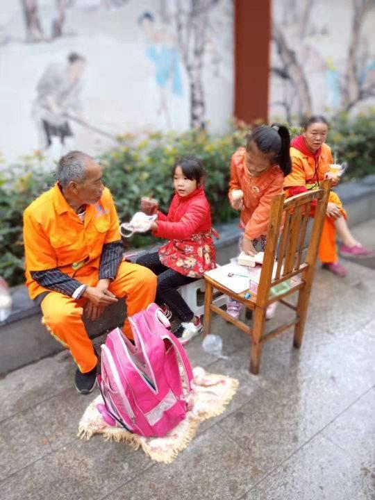 环卫工夫妻国庆上班 带着7岁女儿在街边做作业
