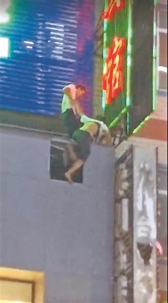少女坠楼悬挂广告牌 四名男青年合力营救