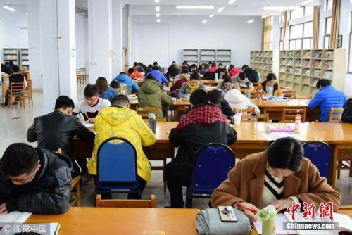 资料图:2017年11月22日,山东青岛,考研生在图书馆内埋身书海认真复习。小老茂 摄 图片来源:视觉中国