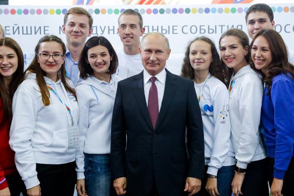 普京出席俄罗斯体育强国论坛 与美女志愿者簇拥合影