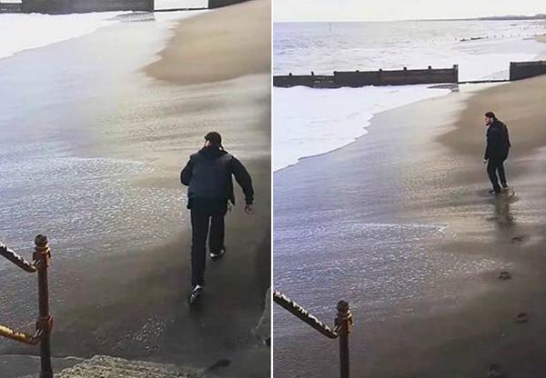 英男子沙滩上和潮水赛跑被浇成落汤鸡