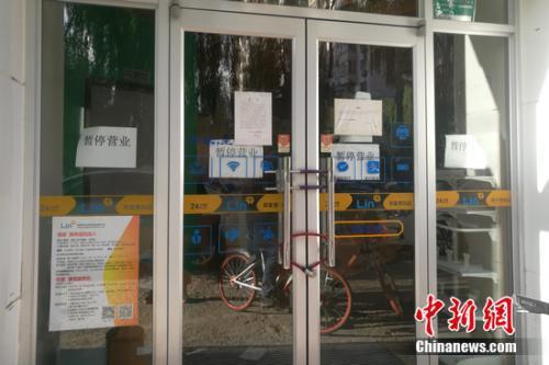 北京街边的某邻家便利店大门紧锁,并张贴着暂停营业的公告。谢艺观 摄
