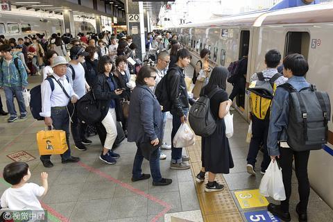 """2018年""""黄金周""""期间,在东京拎着大包小包等车的日本民众"""