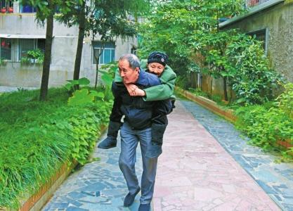 一根背带系牢母亲身 64岁儿子每天背92岁母亲散步