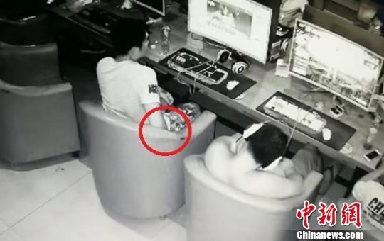 图为:行窃男子将他人手机藏到自己口袋后迅速离开。浙江省天台县公安局供图
