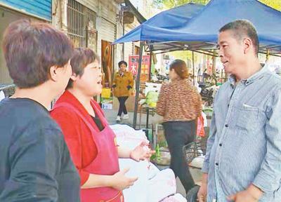资料图片:河北省石家庄市无极县东中铺村村民、退伍军人吕保民(右一)在菜市场与商贩交谈。