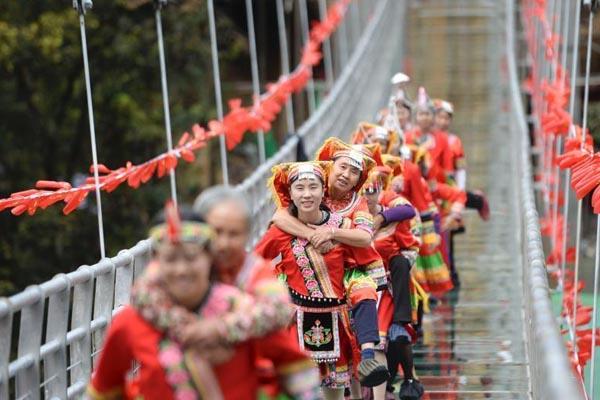 湖南少数民族举行媳妇背婆婆过玻璃桥大赛