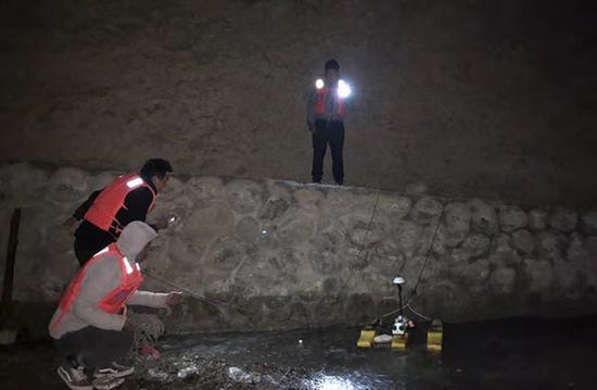 监测人员在夜间打着电筒工作。昌都市水文局图