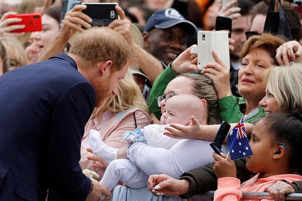 """英哈里王子夫妇抵墨尔本访问 哈里被婴儿""""萌化""""伸手抚摸"""