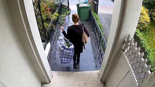 英穿着得体女子被拍偷拿一户人家门口大袋服装