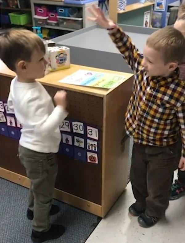 美小学生用拥抱握手碰拳等不同方式问候道别