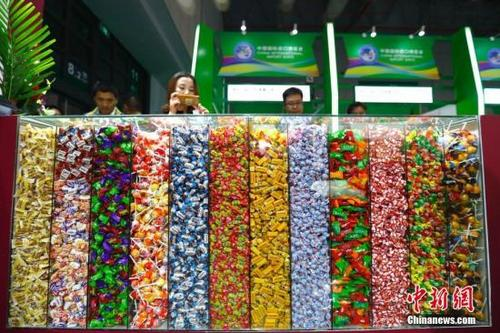 中国侨网资料图:进博会食品及农产品展区内各色糖果吸引观众。中新社记者 富田 摄