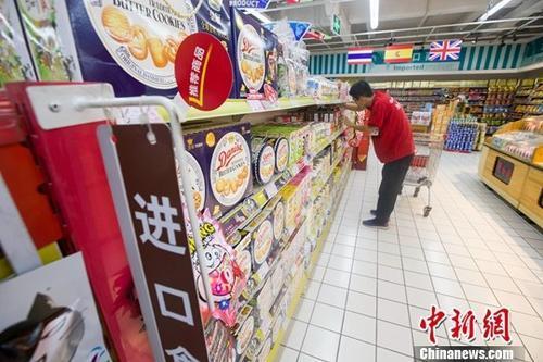 中国侨网资料图:某超市工作人员正在整理商品。中新社记者 张云 摄