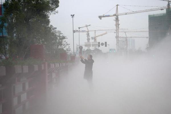 成都街头开启喷雾除霾装置抵御污染天气