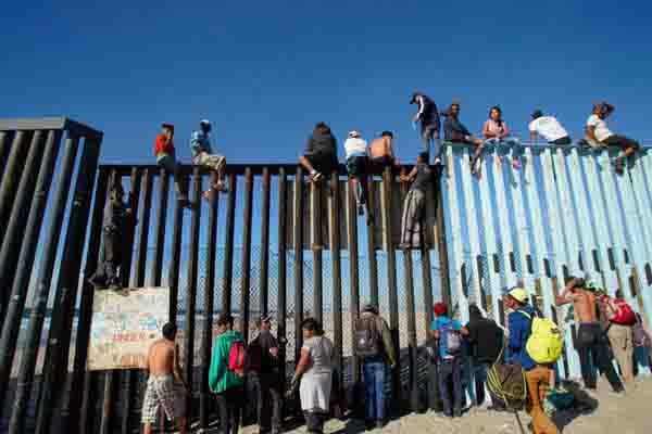 特朗普,我们来了!首批中美洲大篷车移民爬上边境墙