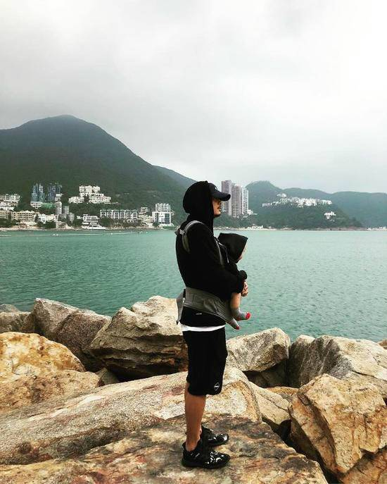余文乐抱儿子看海 两人都身穿黑色帽衫齐看海超酷