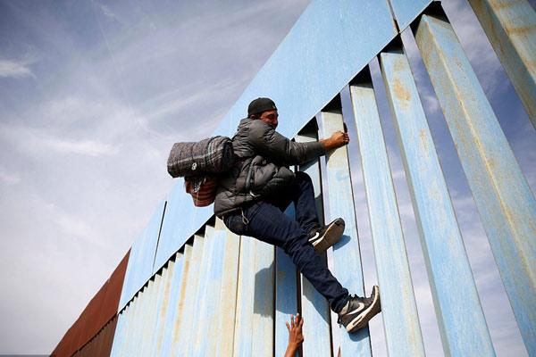 大批中美洲移民持续抵达美墨边境 徒手攀爬边境隔离墙