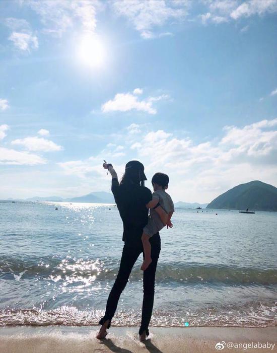 baby感恩节晒与小海绵合影 海边单手抱娃长腿吸睛