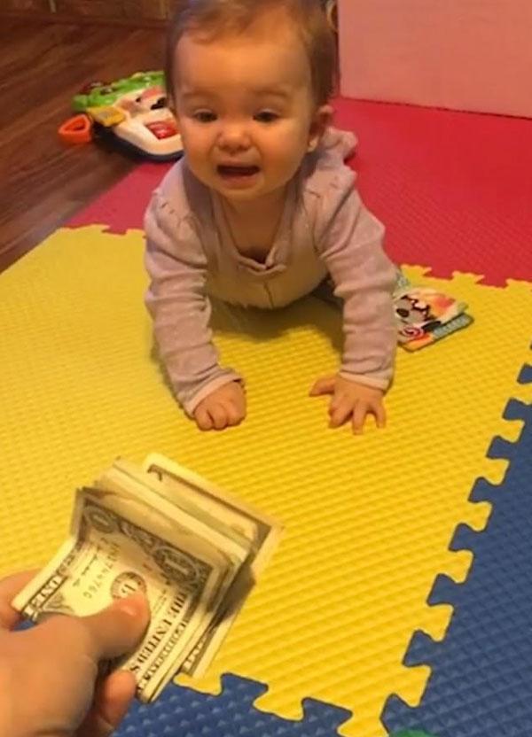 小财迷!美半岁大女婴不爱玩具爱钞票