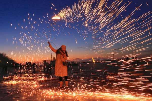 哈尔滨:松花江上游客玩手甩烟花 场面壮观