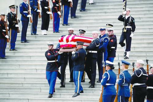 5日,美国前总统老布什的国葬仪式在华盛顿举行。图为仪仗兵将老布什的灵柩抬出国会大厦。
