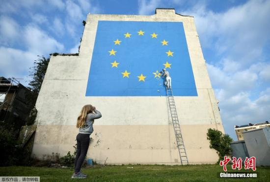 资料图:当地时间2018-12-13,英国多佛,一名街头艺术家班克西创作了一幅画,画面中一名工人正从欧盟12星旗帜上抹掉一颗星,寓意着英国将脱离欧盟。