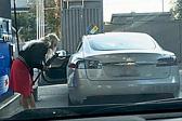 美加油站一女子欲拿油枪给电动汽车加油