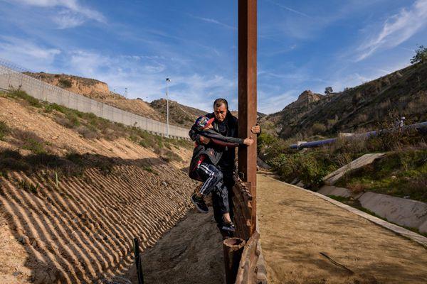 中美洲移民涉险翻越美墨边境墙进入美国