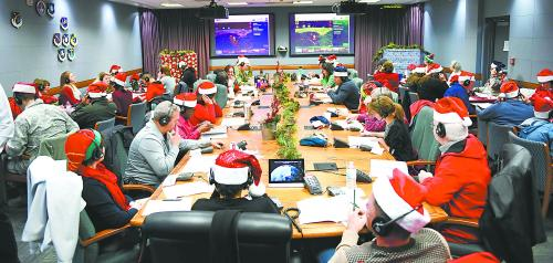 当地时间 24 日,美国军官与自愿者在北美防空司令部接听孩子们打来咨询圣诞老人在那里的炎线电话。