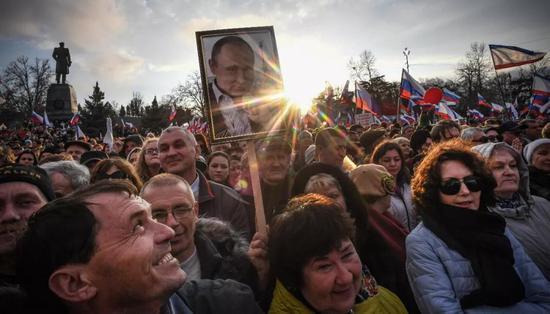 △2018年俄罗斯大选前的竞选活动,俄罗斯民众高举普京照片。