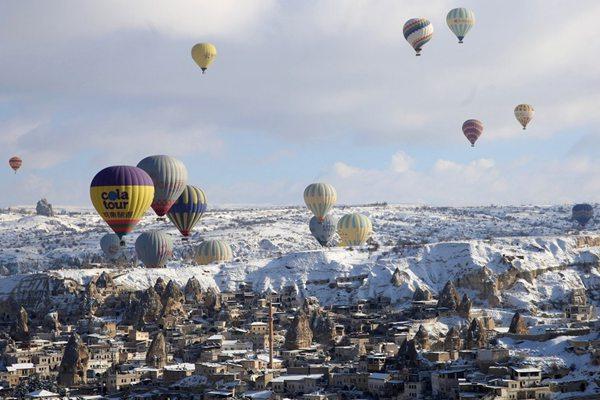 """热气球飞掠雪白""""石柱森林"""" 冬季卡帕多西亚宛若童话世界"""