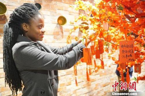 中国侨网图为外国友人在祈福树上挂上祈福牌。 韩章云 摄